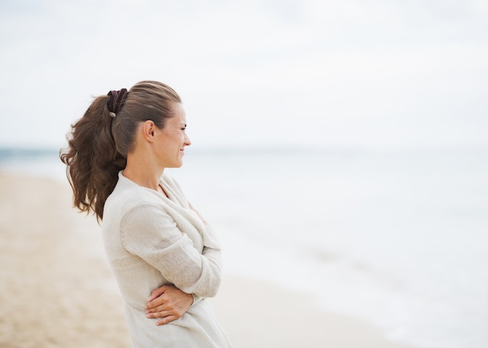 Young woman in sweater on beach looking into distance